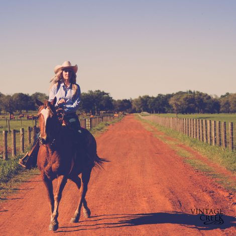 Cowgirl riding a horse. Senior photos on a red dirt road.